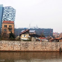 Der Fluss Miljacka fließt zu Füßen einer Romasiedlung. Im Hintergrund prägen neue Bürogebäude das Stadtbild des modernen Sarajevos.