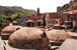 Kuppeln auf dem Dach eines Badehauses in der Altstadt. Im Hintergrund erhebt sich die Festung Narikala und das Minarett einer Moschee.